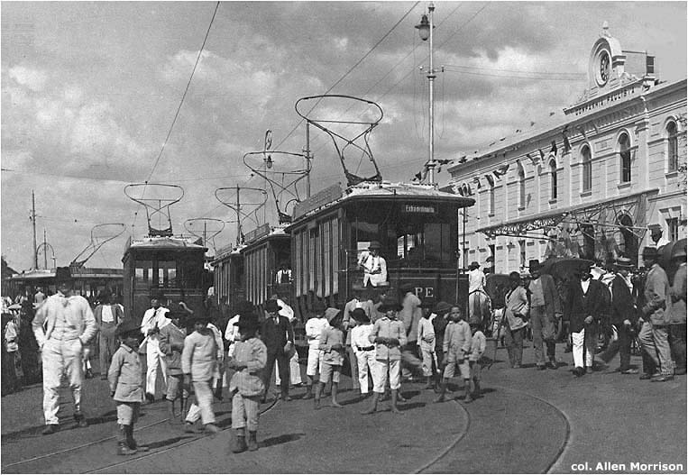 """Inauguração do bonde elétrico São Carlos, em frente à estação ferroviária Paulista, no domingo, 27 de dezembro de 1914 [ver mapa]. Todos os seis carros da frota são mostrados neste modo de exibição. As iniciais """"CPE"""" da Companhia Paulista de Eletricidade são visíveis em alguns."""